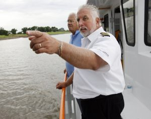 Capt. Monty Compton points out features along the river bank to passenger Bill Kopplin during an Oklahoma River Cruise on the Devon Explorer in Oklahoma City, Wednesday, July 9, 2008. BY NATE BILLINGS, THE OKLAHOMAN